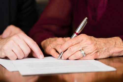 Photo: Elder Woman Signing Will Under Undue Influence - Dave Burns Law Office, LLC