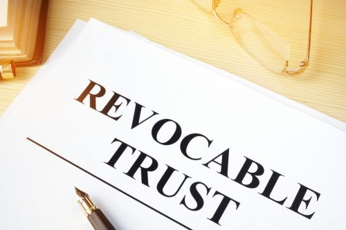 Revocable trust on a wooden desk. - Dave Burns Law Office, LLC