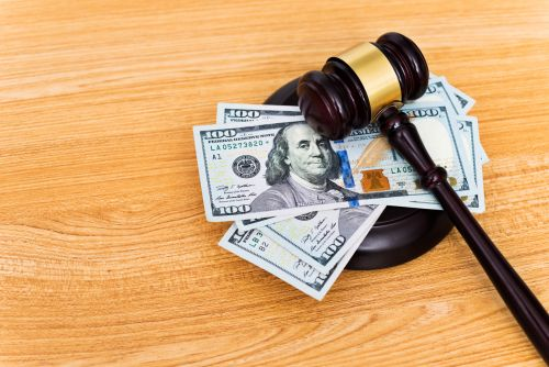 US dollar bills and a gavel on the table.